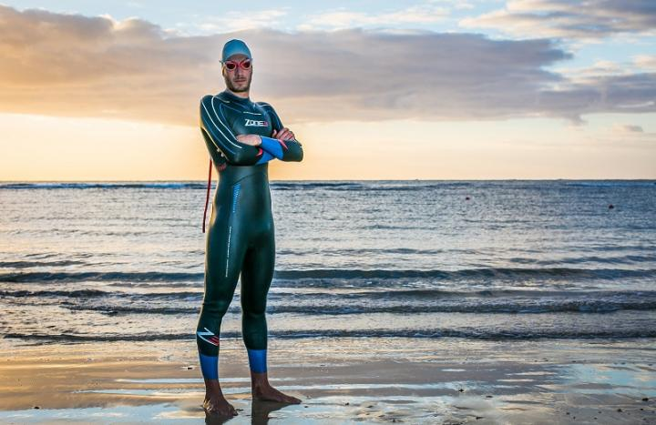A man, wearing a swim cap and googles, modeling a Zone3 wetsuit on a beach