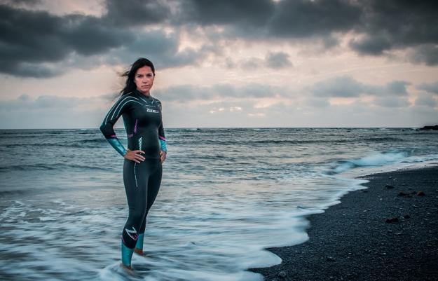 A woman modeling a Zone3 wetsuit in the ocean swash