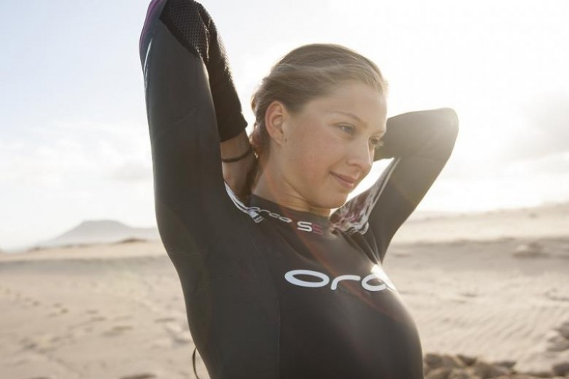 A woman on a beach in an Orca wetsuit