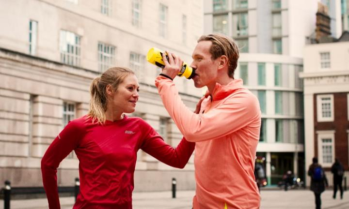 Two runners standing in an urban setting, one is drinking from a bottle