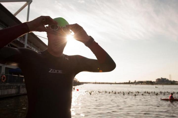 A man wearing a Zone3 wetsuit looking at the camera while the sun beams through his fingers
