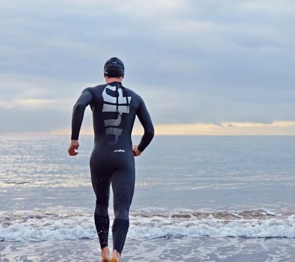 man running into sea wearing dhb wetsuit