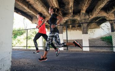 man and women running under bridge wearing adidas gear