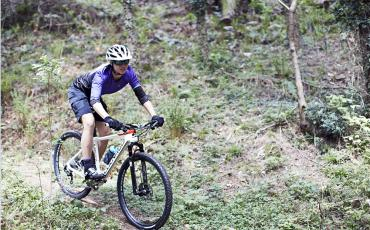 image of woman mountain biking in woodland