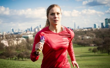image of runner running in park holding High5 gel