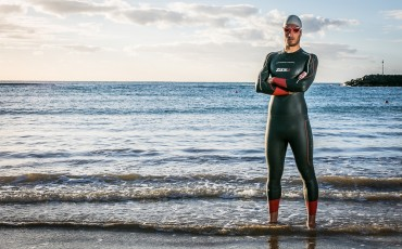 A man, wearing a swim cap and googles, modeling a Zone3 wetsuit