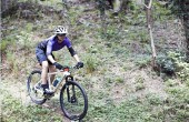 image of woman mountain biking in woodland