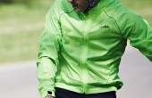 A cyclist wearing a green dhb waterproof jacket
