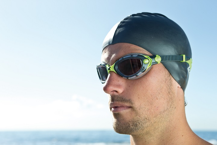 A swimmer out of the water wearing a Zoggs swim cap and goggles