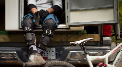 A mountain biker seated with body armour gear on their lower legs