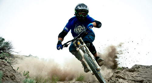 A mountain biker in action kicking up dirt on their bike