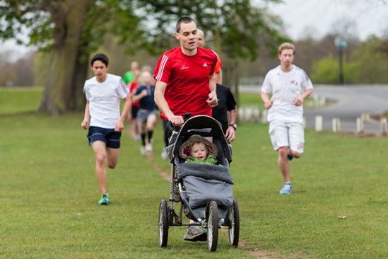 A man jogging while pushing a child in a pushchair during a parkrun