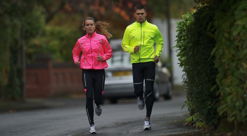 A male and female jogger running side by side